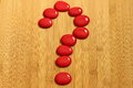 A question mark made with red pebbles in Zen lifestyle on a brown bamboo floor