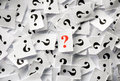 Question marks lot of on white papers hard light Stock Photo