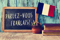 Question parlez vous francais do you speak french a chalkboard with the written in a pot with pencils and the flag of Royalty Free Stock Photos