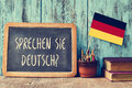 Question sprechen sie deutsch do you speak german a chalkboard with the written in a pot with pencils some books and the Stock Image