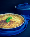 Quiche lorraine pie with chicken mushrooms and broccoli in blue round baking form on wooden background a piece of french Royalty Free Stock Photography
