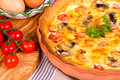Quiche supper homemade savory in terracotta dish with olive wood chopping board cherry vine tomatoes and fresh eggs Royalty Free Stock Images