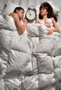 Quiet young couple sleeping together ignoring alarm clock bell Royalty Free Stock Photos