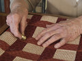 Quilting hands elderly quilter pushing needle with thimble Royalty Free Stock Photo