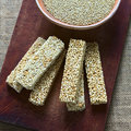 Quinoa cereal bars overhead shots of one with honey the other mixed with amaranth with bowl of raw white on wooden board Royalty Free Stock Photo