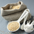 Quinoa grain in small burlap sack and porcelain measuring spoons on gray background Stock Image