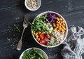 Quinoa and spicy chickpea vegetable vegetarian buddha bowl. Healthy food concept. On a dark background Royalty Free Stock Photo