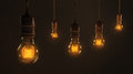 Quintet of vintage light bulbs a hanging over a dark brown background Royalty Free Stock Photography