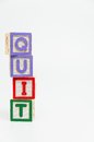 QUIT word wooden block arrange in vertical style on white background and selective focus Royalty Free Stock Photo