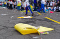 QUITO, ECUADOR - JULY 7, 2015: Yellow cardboard in the street, lots of garbage after an event, peple behind trying to Royalty Free Stock Photo