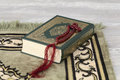 The quran and the prayer beads on a carpet Stock Photo