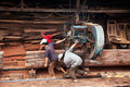 Carpenter pull power-saw at sawmill. QUY NHON, VIE Royalty Free Stock Photo