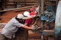 Carpenter push power-saw at sawmill. QUY NHON, VIE Royalty Free Stock Photo