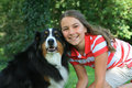 Qv s girl with australian shepherd dog smiling looking forward at the camera Stock Images