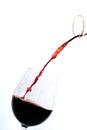 Rött vin som häller in i ett exponeringsglas Arkivbild