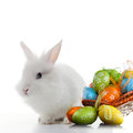 Rabbit and color easter eggs in basket isolated on white Stock Images