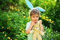 Rabbit kid with bunny ears. Hare toy. Egg hunt on spring holiday. love easter. Family holiday. Little boy child in green Royalty Free Stock Photo