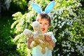 Rabbit kid with bunny ears. Hare toy. Little boy child in green forest. Egg hunt on spring holiday. love easter. Family Royalty Free Stock Photo