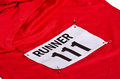 Race number bib attached to front red running shirt Royalty Free Stock Images