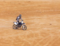 Racer on a motorcycle ride through the desert in summer Royalty Free Stock Image