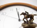 Racing against time figure of jockey riding racehorse with out of focus clock in the background Royalty Free Stock Image