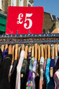 Rack of dresses at market bargain for a fiver second hand clothes for sale recession theme Stock Images