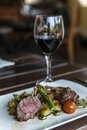 Rack of lamb and a glass red wine on table Stock Photo