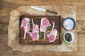 Rack of Lamb with rosemary and spices on rustic chopping board over oily craft paper, old wooden background Royalty Free Stock Photo