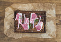 Rack of Lamb with rosemary and spices on rustic chopping board over oily craft paper, old wooden background. Royalty Free Stock Photo