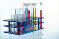 Rack with test tubes of colorful fluids on a white background Stock Images