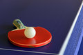 Racket and ball on table tennis table blue red white Stock Photography