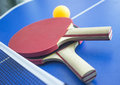 Racket for ping pong red background toy table games activity paddle sport bat yellow tennis ball equipment playback wooden table Royalty Free Stock Image