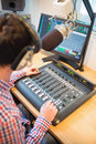 Radio host using sound mixer on table cropped image of in studio Royalty Free Stock Image