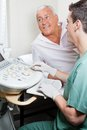 Radiologic technologist with patient senior looking at ultrasound machine Royalty Free Stock Photo