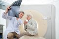 Radiologist with patient looking at ct scan mature male an elderly female results Stock Photo