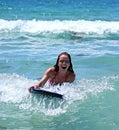 Ragazza che sorride mentre guidando una grande onda blu su una scheda del corpo sul mare blu un giorno pieno di sole. Fotografia Stock Libera da Diritti