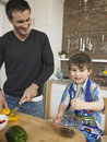 Ragazzo e padre felici cooking food together in cucina Immagine Stock