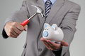 Raiding the piggy bank businessman with hammer about to smash to get at corporate savings Stock Images
