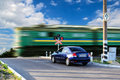 Rail crossing with a moving train and waiting car Royalty Free Stock Image