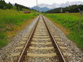 Rail route to mountains mountain landscape at summer with a straight lined railway track leading into the alps bavaria germany Royalty Free Stock Image