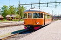 Railcar orange and yellow standing with open doors at railway platform with station area in background lovely small house to the Stock Photos