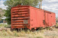Railroad boxcar with a bit of rust parked behind some homes notice the three wood steps for help getting in Royalty Free Stock Image