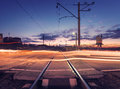 Railroad crossing with car lights in motion at night Royalty Free Stock Photo