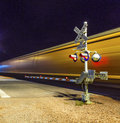 Railroad crossing with passing train by night Royalty Free Stock Photo