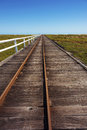 Railroad tracks lead distance along long wooden boardwalk over floodplains Royalty Free Stock Image