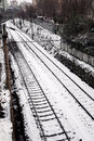 Rails in the snow covered with also some buildings and trees are visible Royalty Free Stock Images