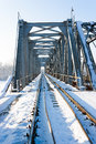 Railway bridge railroad tracks covered in snow going through an iron Royalty Free Stock Photo