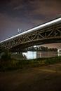 Railway bridge in warsaw poland by night train with lights and dark sky national stadium vistula river illuminated Stock Images