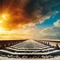 Railway closeup to horizon under sunset colored sky in Stock Image