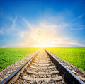 Railway in field to the sun through green Royalty Free Stock Photography